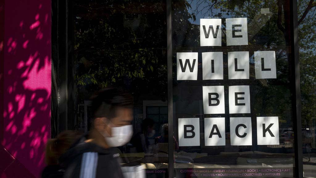 """A pedestrian wearing a protective mask walks past a """"We Will Be Back"""" sign in a window of a closed store on Mission Street in San Francisco, California, U.S., on Wednesday, April 15, 2020"""