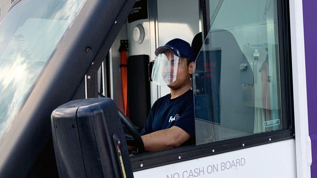 A FedEx employee wears a baseball cap face shield designed by Loggerhead Tools founder Dan Brown.