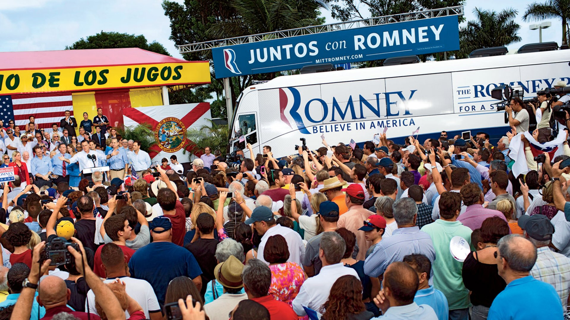 <b>Rallying the Troops</b> Mitt Romney at a campaign stop outside a Miami juice stand. The sign above the bus translates to <i>Together With Romney.</i>