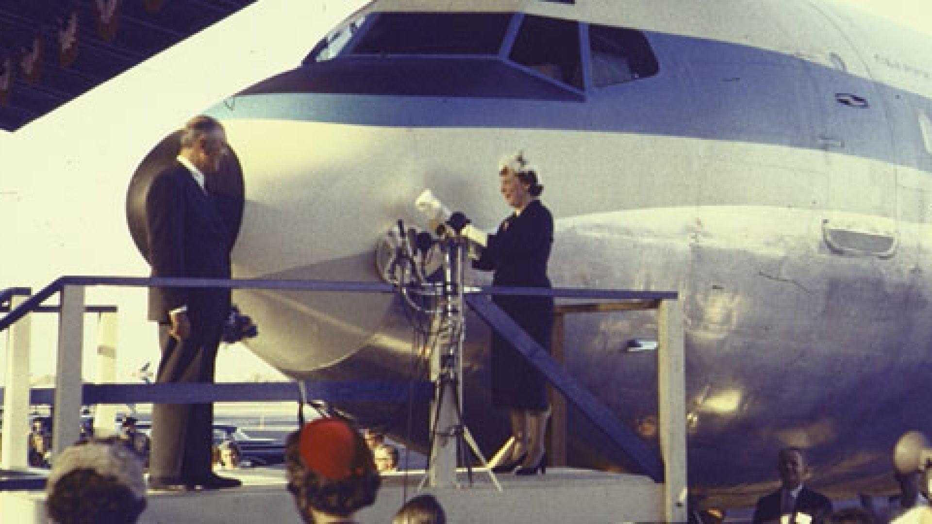 Mrs. Dwight Eisenhower christening Pan Am's Boeing 707 America at Natl. Airport as Pan Am Pres. Juan Trippe looks on.