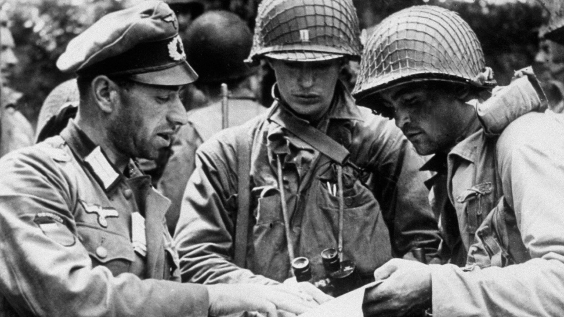 A German officer explains details of a military map captured with him, to members of the Allied Expeditionary Force.