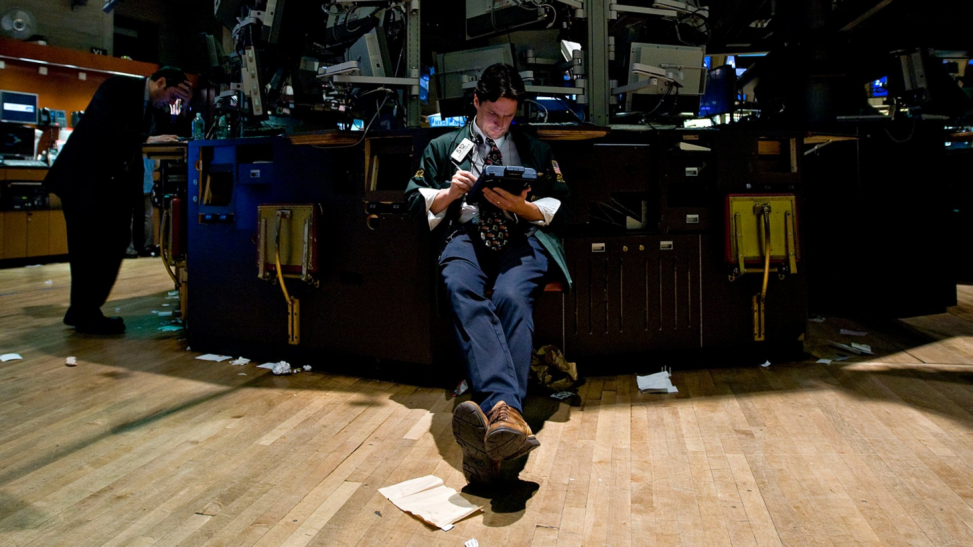A trader works at a vacant post on the floor of the New York Stock Exchange.
