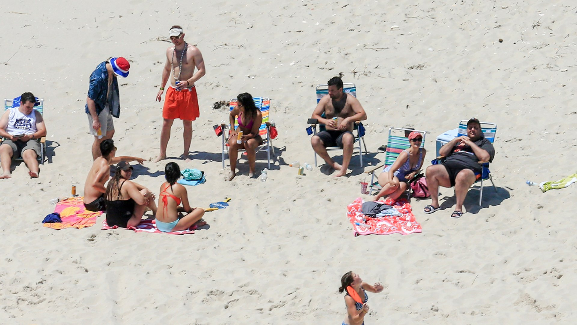 """New Jersey governor Chris Christie, right, uses the beach with his family and friends at the governor's summer house at Island Beach State Park in New Jersey. Christie is defending his use of the beach, closed to the public during the state's government shutdown, saying he had previously announced his vacation plans and the media had simply """"caught a politician keeping his word."""""""