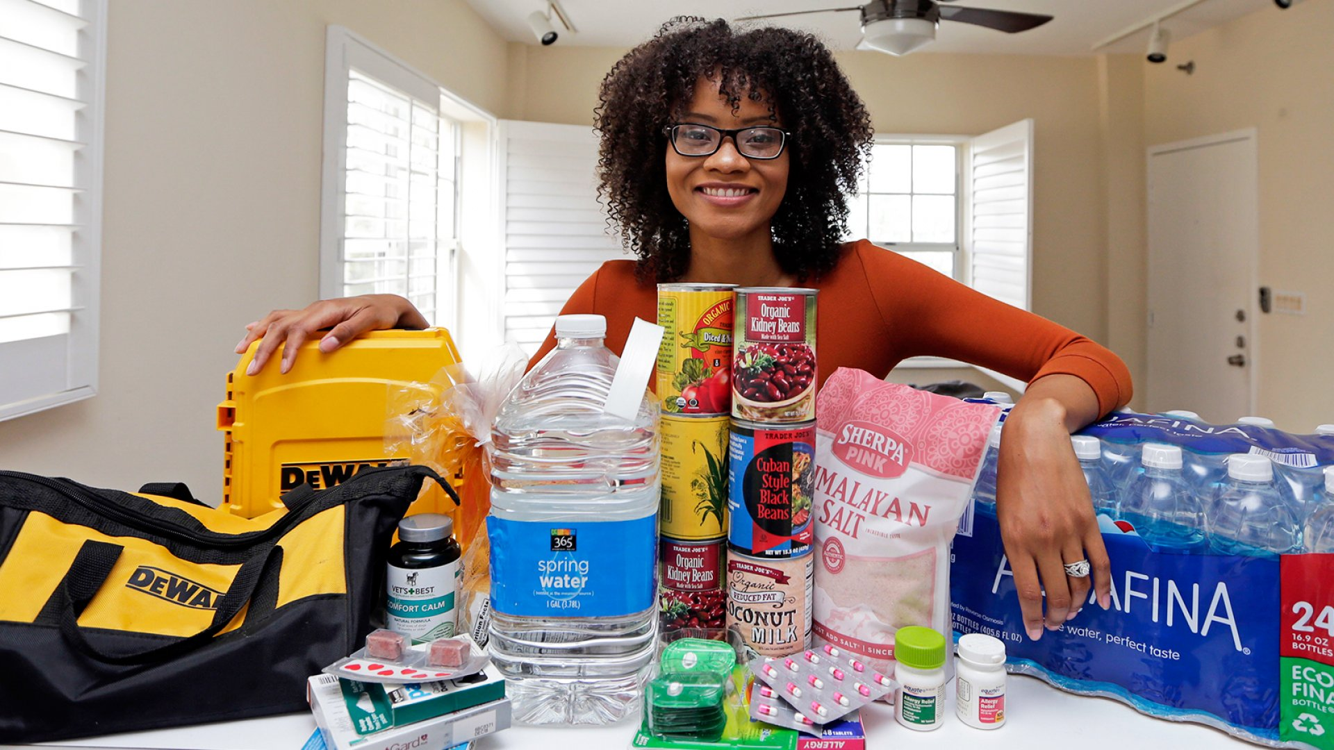 In this Friday, Sept. 29, 2017, photo, Lexi Montgomery poses with supplies she has purchased in the event of another storm, in Miami Beach, Fla. Hurricane Irma was the first hurricane that Montgomery ever experienced.