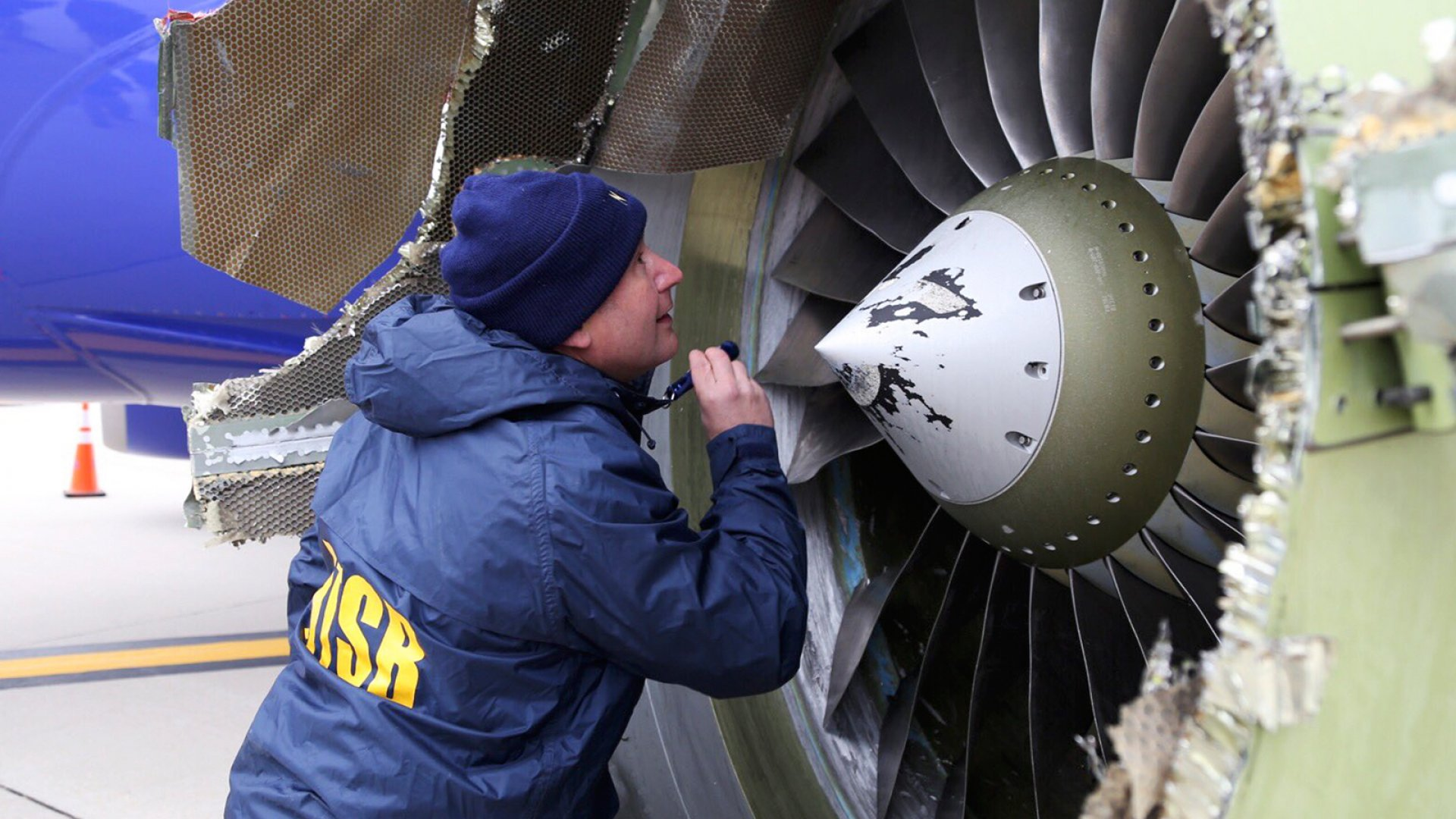 "In this Tuesday, April 17, 2018 photo, a National Transportation Safety Board investigator examines damage to the engine of the Southwest Airlines plane that made an emergency landing at Philadelphia International Airport in Philadelphia. A preliminary examination of the blown jet engine of the Southwest Airlines plane that set off a terrifying chain of events and left a businesswoman hanging half outside a shattered window showed evidence of ""metal fatigue,"" according to the National Transportation Safety Board."