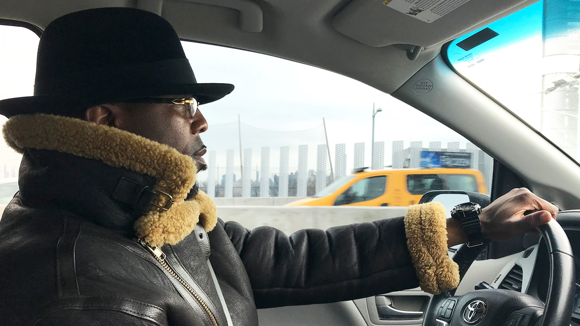 Calvin Buari at the wheel. He used to drive a BMW and sell crack. Now he drives a minivan and hopes to build his small transportation company into a multimillion-dollar enterprise.
