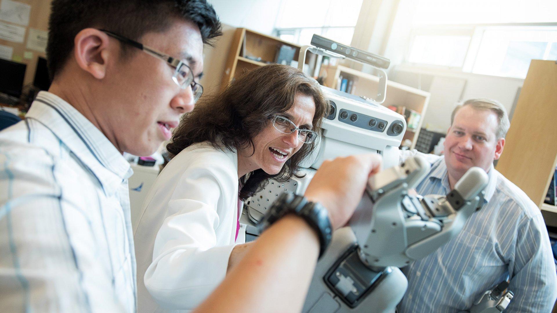 Mechanical engineering professor Elizabeth Croft (center) and her team are training robots to work alongside humans