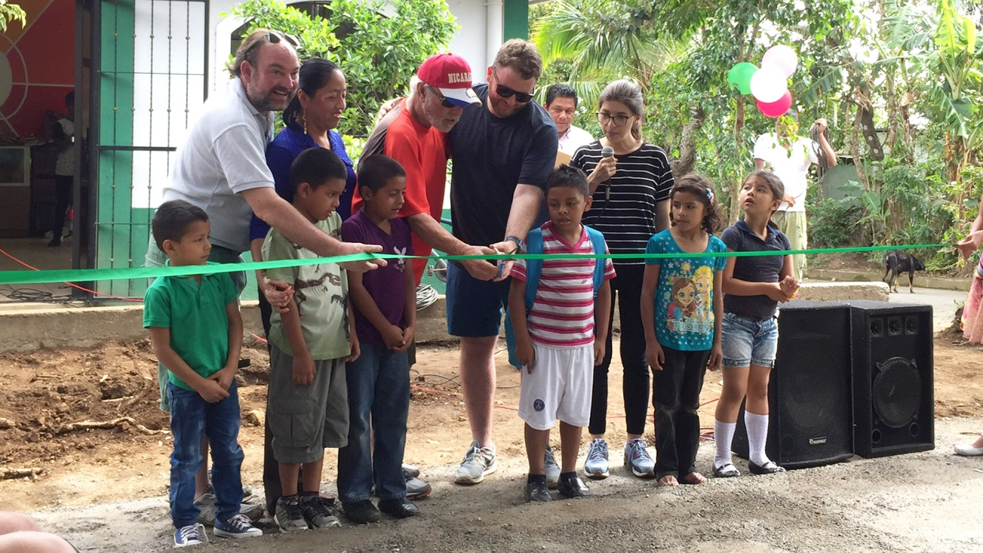 CEO of Fabretto Kevin Marinacci (back left), Ed Ciperski, father of Zachary Ciperski, and President of Elite SEM Zach Morrison are joined by Fabretto staff, volunteers and children at the ribbon-cutting ceremony for the pavilion next to the Zach Ciperski library in San Juan de Oriente, Nicaragua.