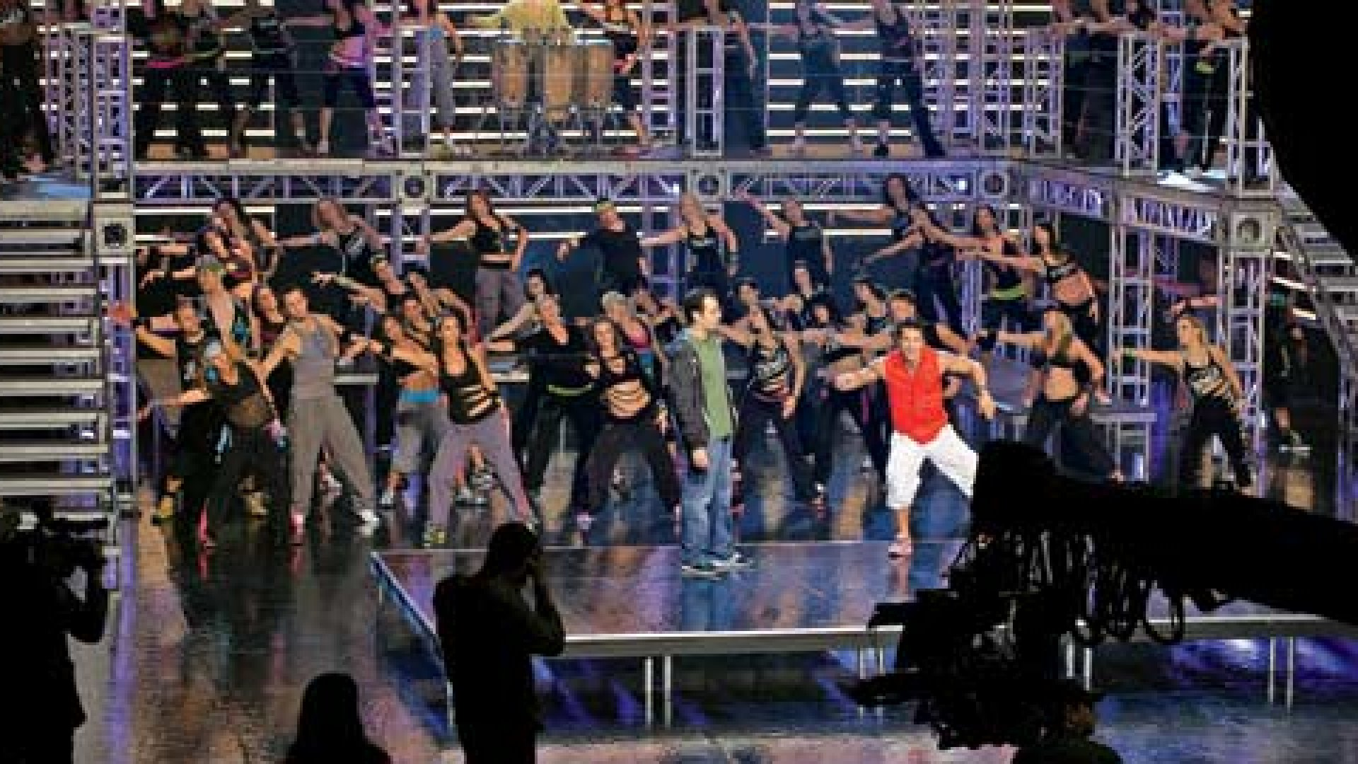 """Alberto (""""Beto"""") Perez, in red, leads a Zumba video shoot. Onstage with him is Alberto Perlman."""