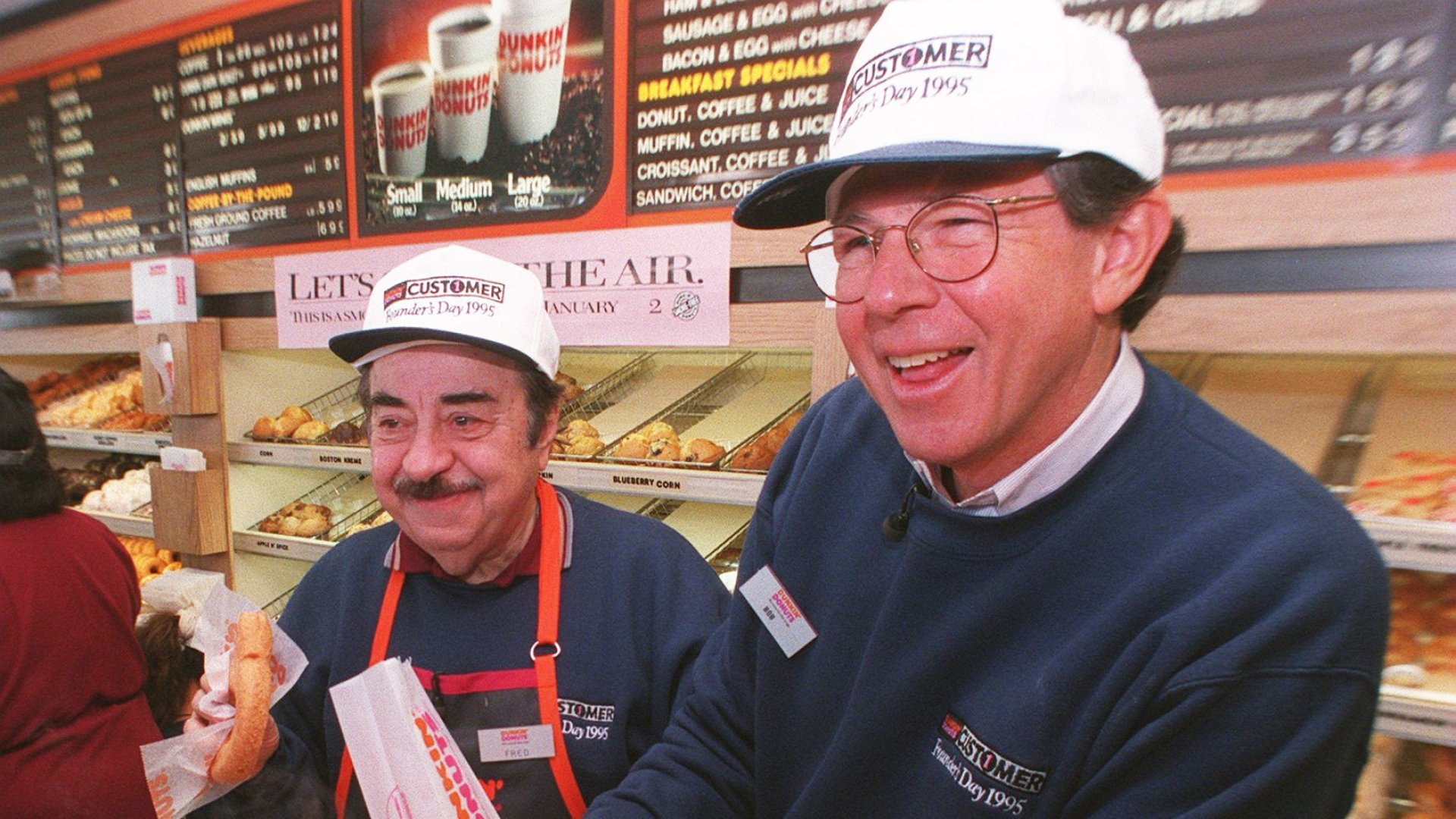 """Dunkin' Donuts CEO Bob Rosenberg pours a customer coffee as actor Michael Vale, who plays """"Fred the Baker"""" in TV commercials, gets ready with a donut at the original Dunkin' Donuts location in Quincy, Massachusetts on January 31, 1995."""