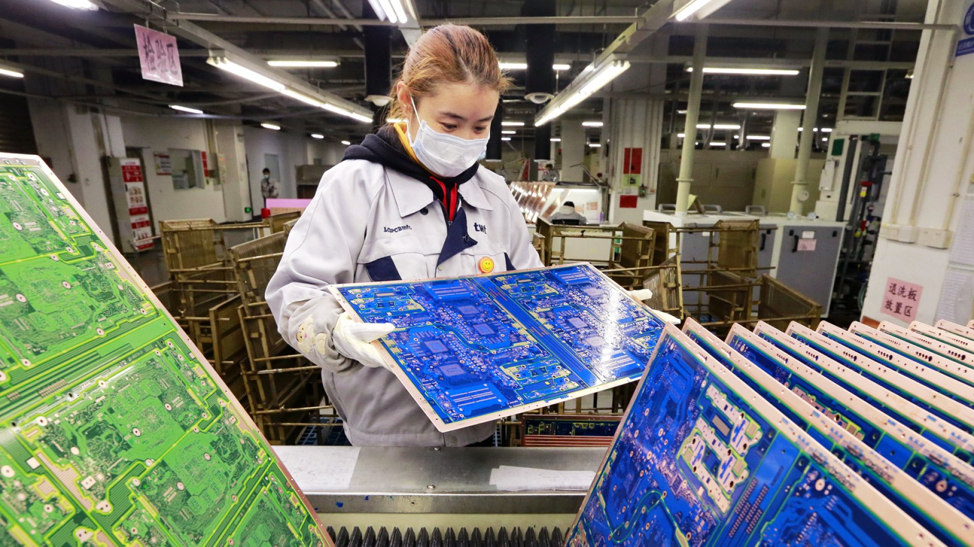 On February 15, 2020, a woman works in a factory of printed circuit boards, a subsidiary of Taiwan PCB Techvest, in Suining, a city in southwest China's Sichuan province.