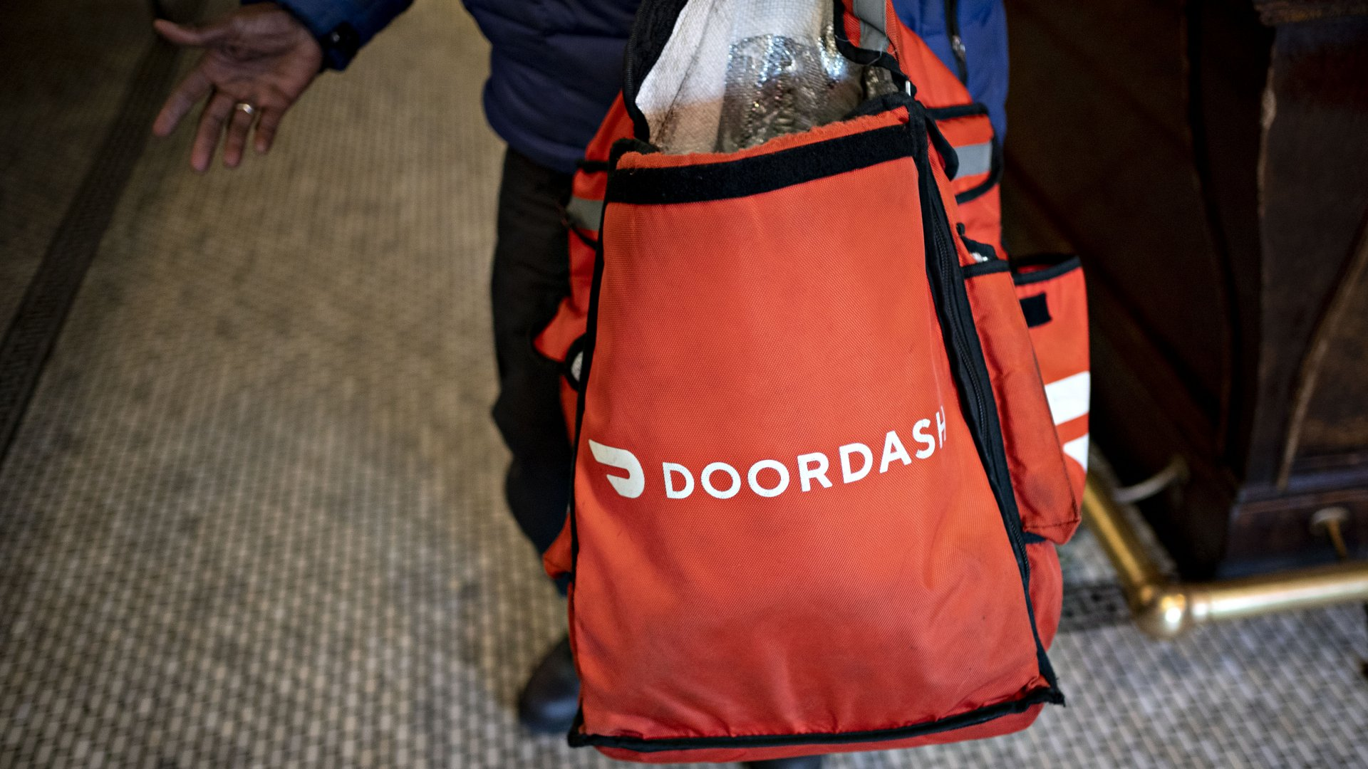 A DoorDash Inc. delivery person holds an insulated bag at a restaurant in Washington, D.C.