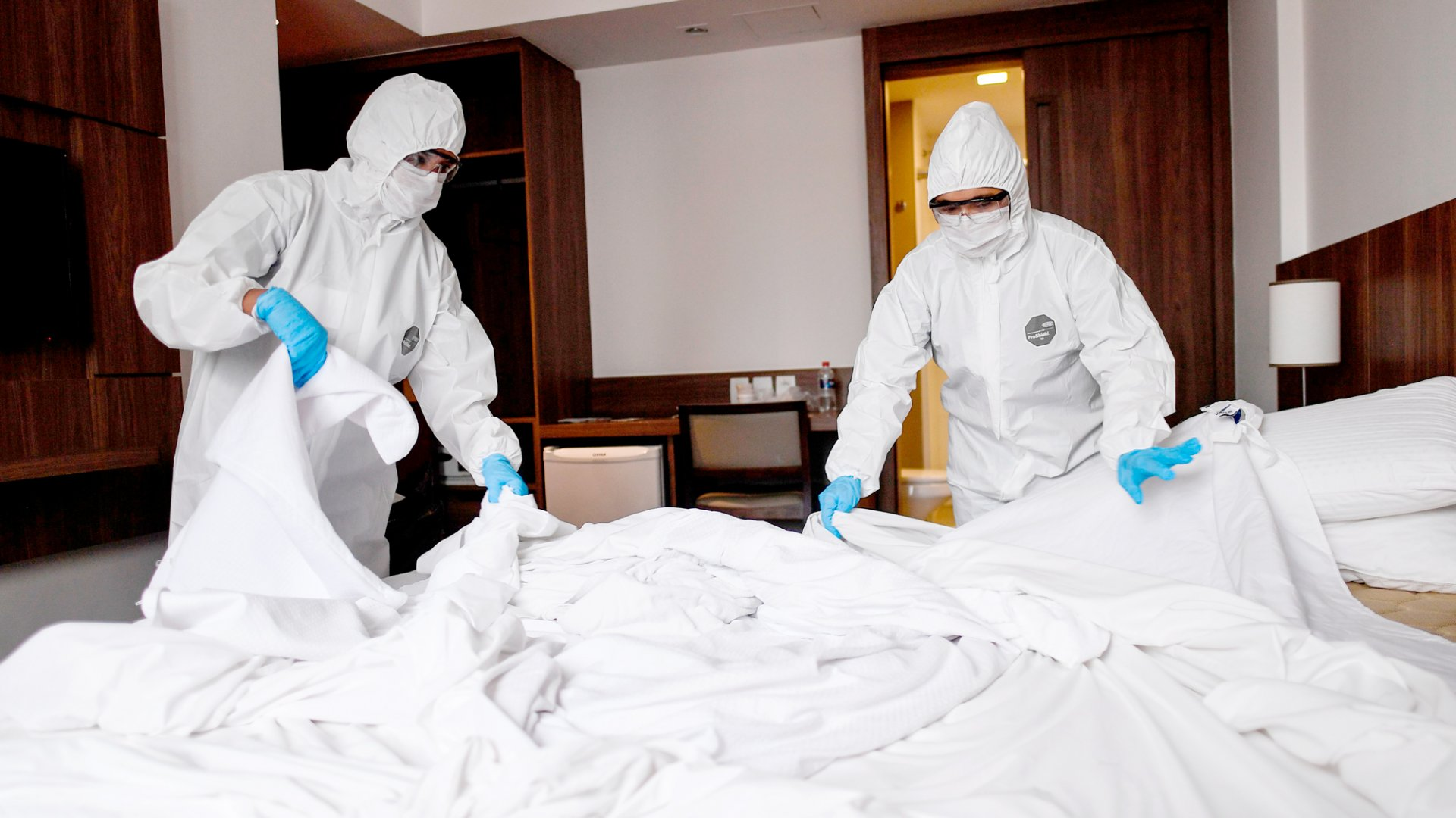 Members of the cleaning staff disinfect a room at a hotel in Belo Horizonte, Brazil on April 7, 2020. The hotel took measures such as the check-in and the check-out are done virtually, all the employees stay inside the hotel and as soon as a room is vacated, it remains closed for 72 hours after being cleaned and disinfected.