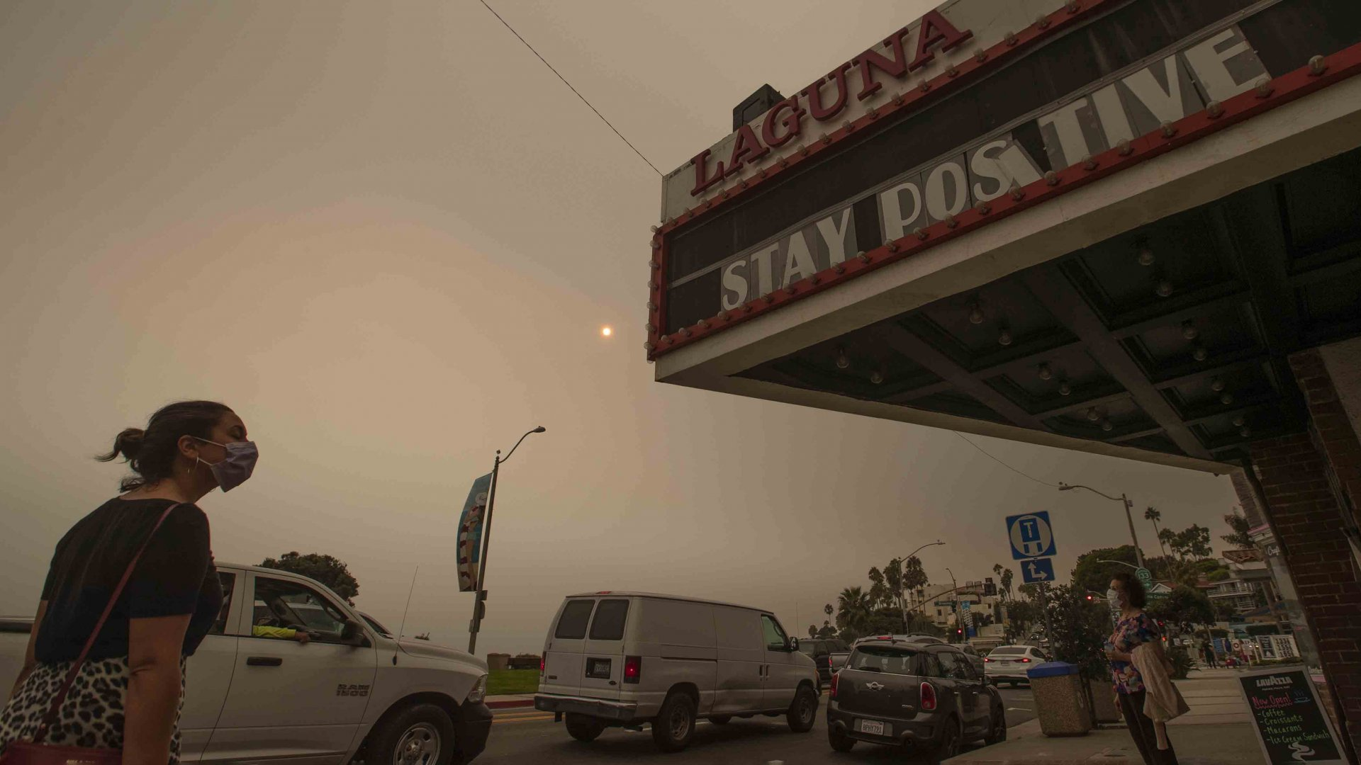 A woman walks past the The South Coast Cinemas building as the sun and sky are partially obscured with ash from Southland wildfires in Laguna Beach Thursday, Sept. 10, 2020.