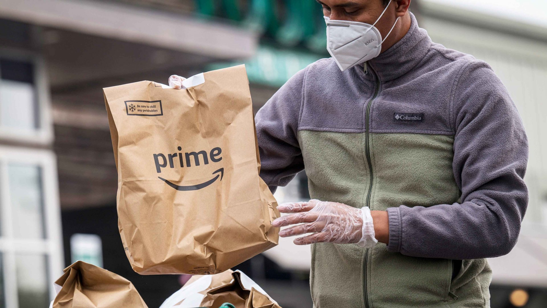 An independent contractor loads Amazon Prime grocery bags into a car outside a Whole Foods Market in Berkeley, California.