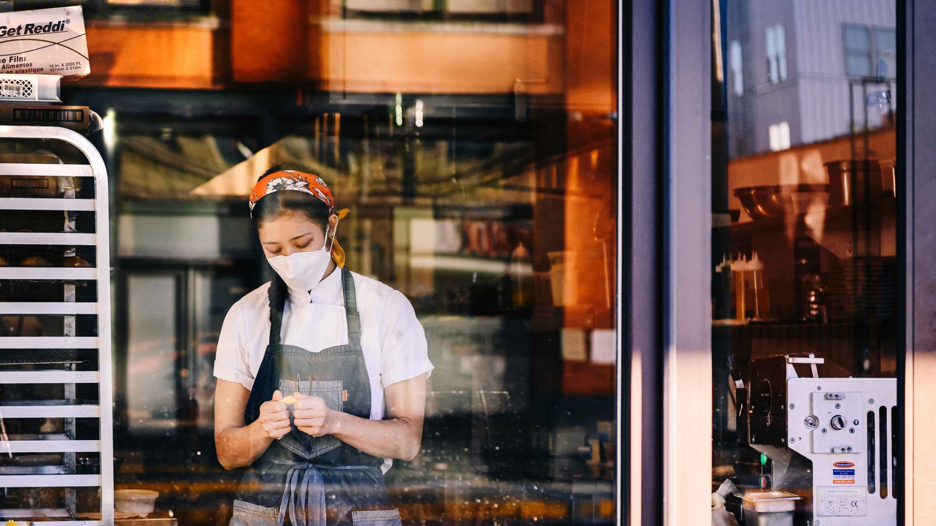 A worker wears a protective mask while preparing food at a restaurant in downtown Memphis.