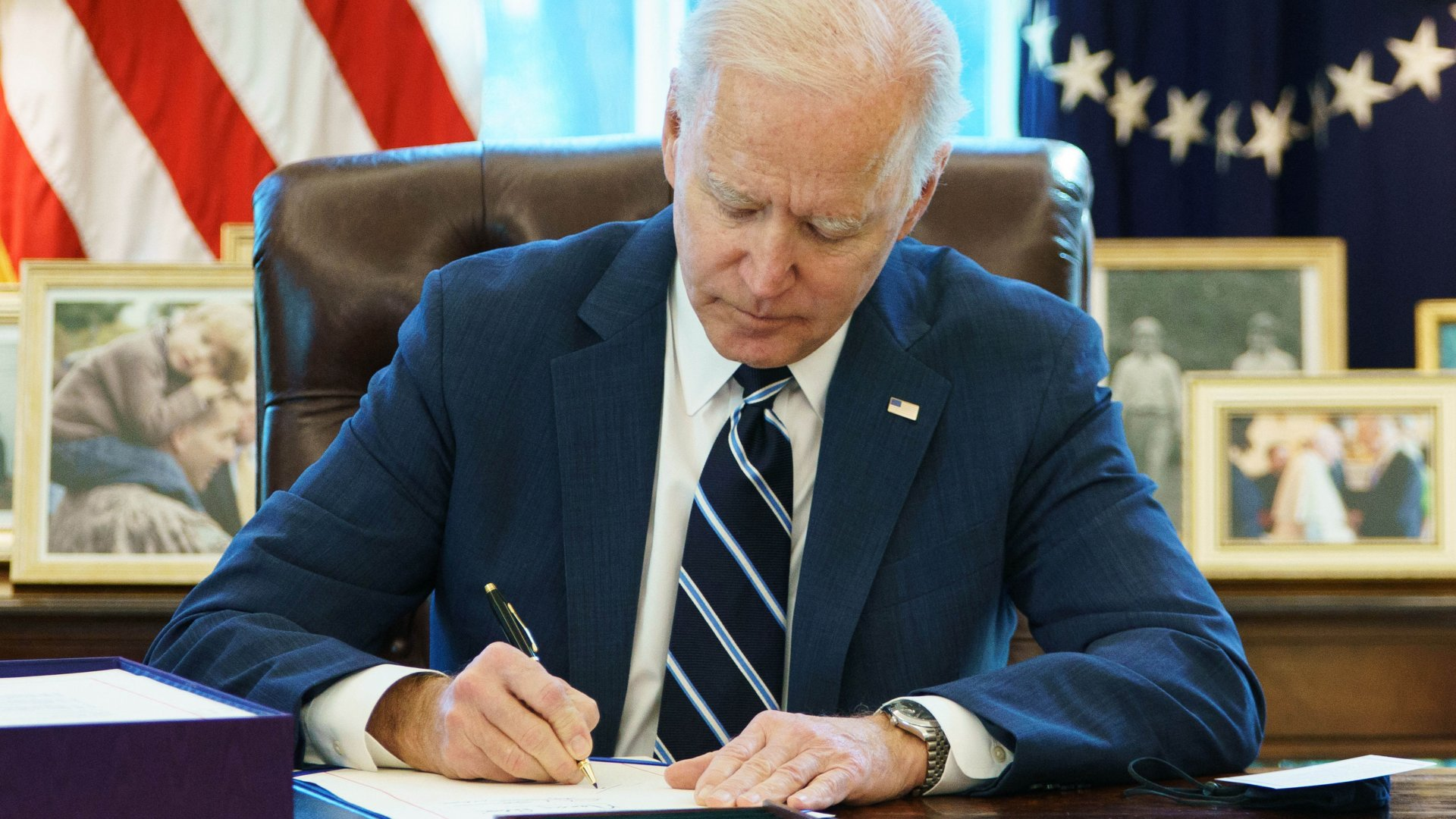 US President Joe Biden signs the American Rescue Plan on March 11, 2021, in the Oval Office of the White House in Washington, DC. - Biden signed the $1.9 trillion economic stimulus bill.