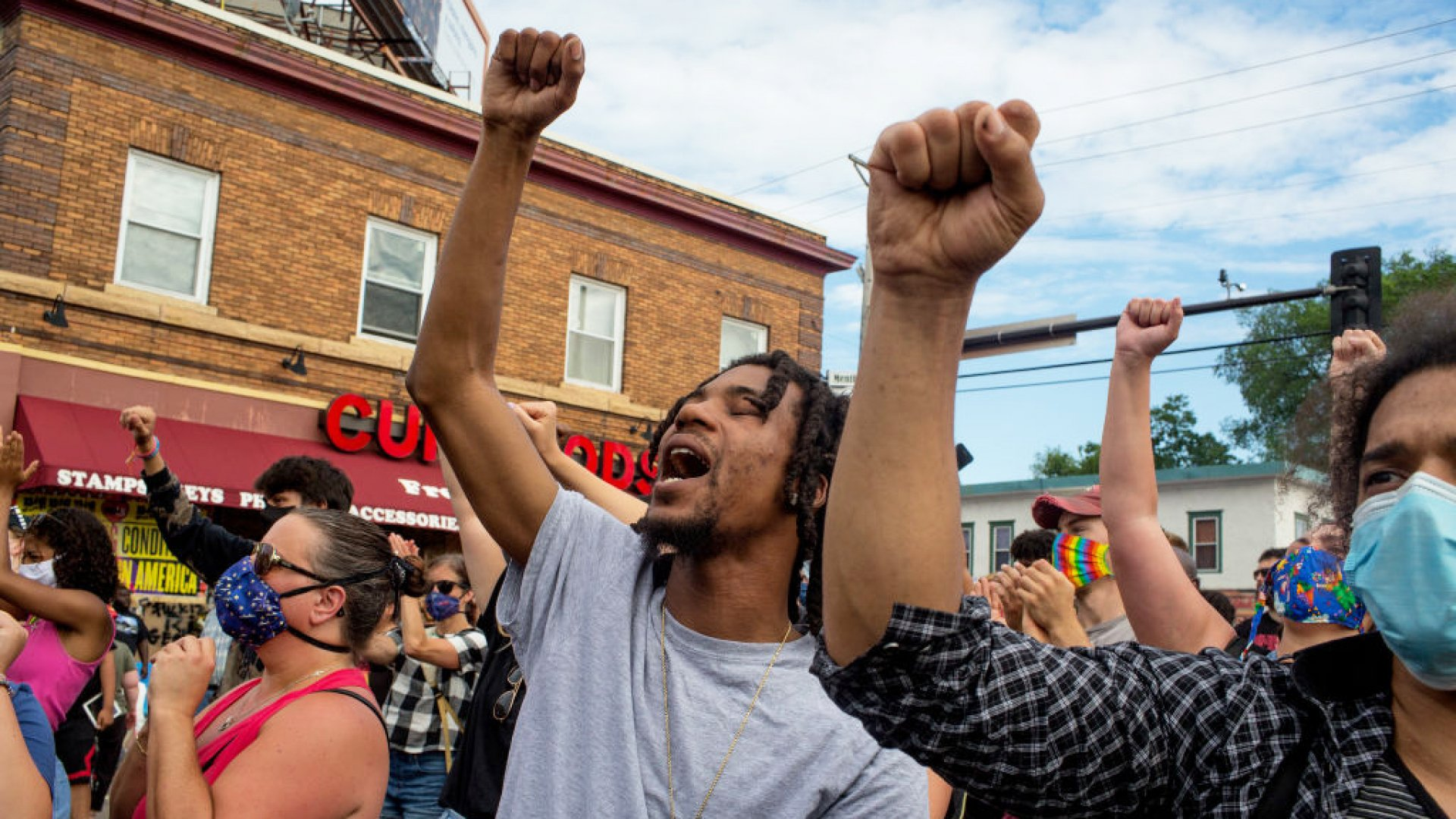 People shout slogans and lift their fists at the memorial site where George Floyd was killed by a police officer on June 4, 2020, outside a chapel at North Central University in Minneapolis, Minnesota.