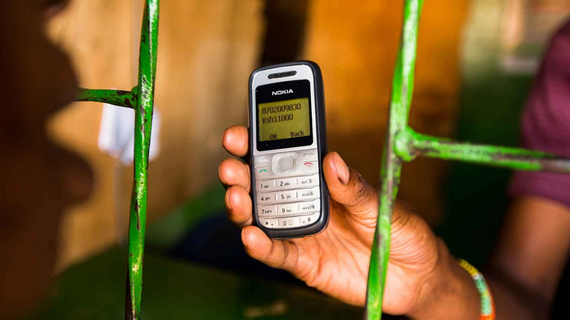 An employee displays a Nokia 1200 mobile phone to a resident as they transfer money using the M-Pesa banking service in Nairobi, Kenya, on Sunday, April 14, 2013.