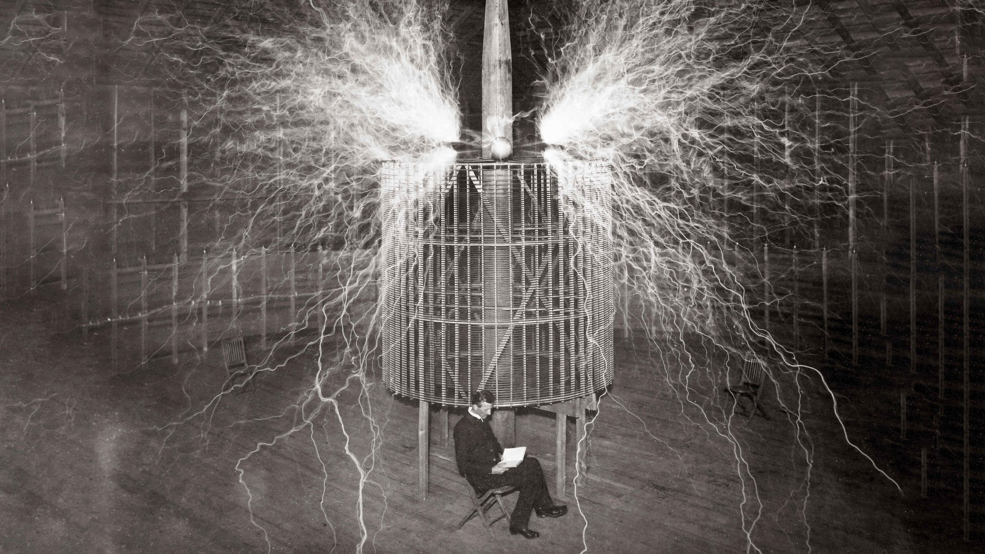 """Nikola Tesla, Serbian-American physicist sitting in his Colorado Springs laboratory with his """"Magnifying transmitter"""""""