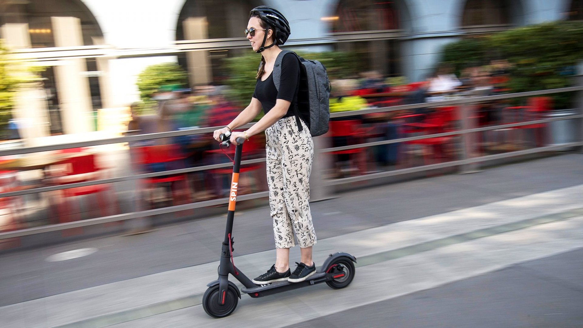 A person rides a Skinny Labs Inc. SpinBike shared electric scooter on the Embarcadero in San Francisco, California.