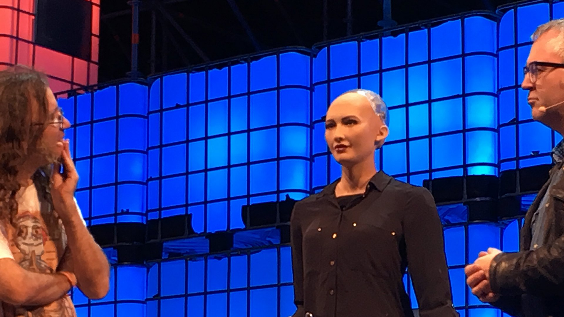 Sophia, an artificially intelligent robot, speaks with Ben Goertzel, AI researcher (left) and Mike Butcher (right), from TechCrunch, at this week's Web Summit in Lisbon.