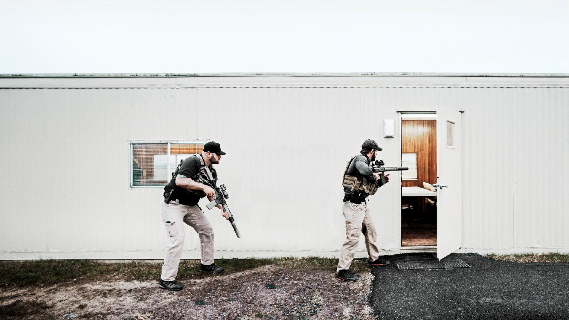 "Two Patriot Group employees--one a veteran of the Air Force and the other an ex-Marine--practice SWAT-like ""room-clearing techniques"" to be used in hostile environments, at a training facility in Midland, Virginia."