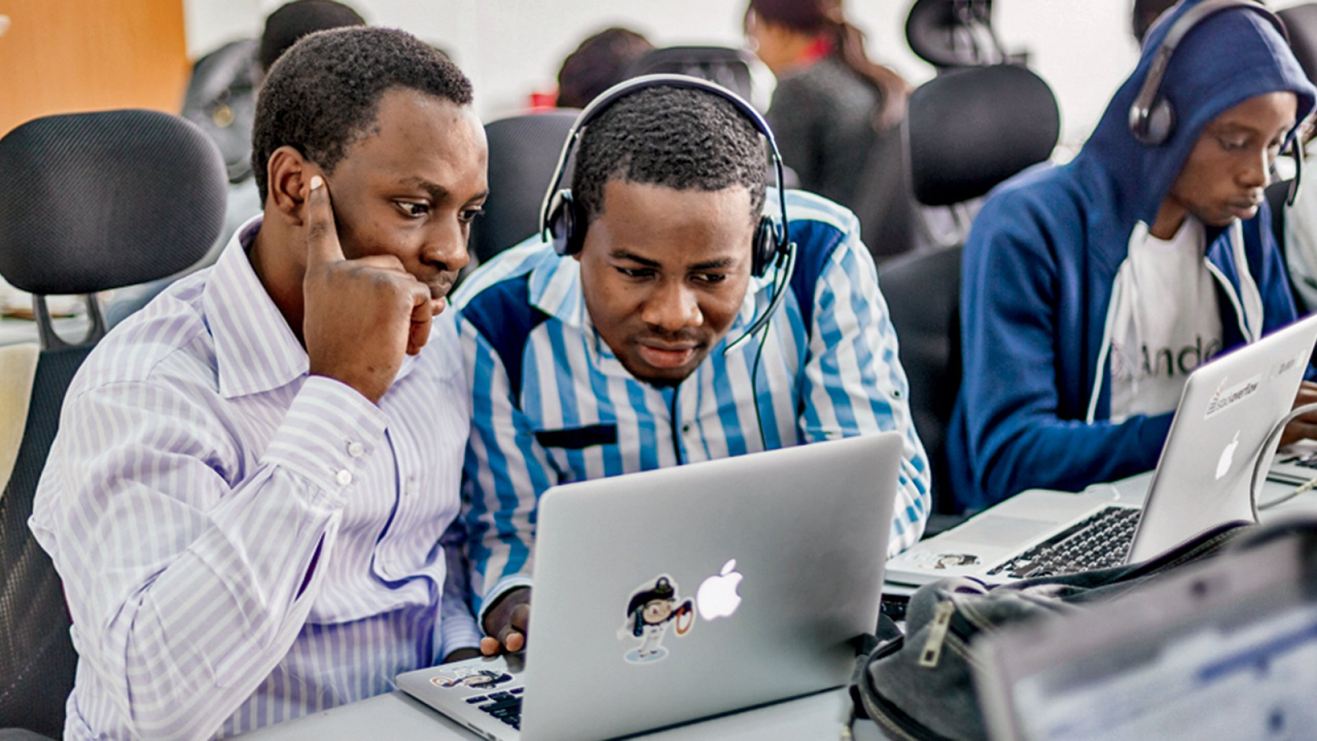 Kayode Adeniyi, Stephen Sunday, and Alex Onozor (blue sweatshirt), students from Nigeria, study at an Andela class.