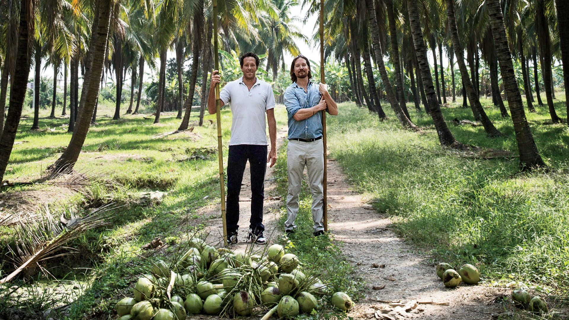 Douglas Riboud (left) and Justin Guilbert at a farm in Thailand where Harmless Harvest coconuts are grown.