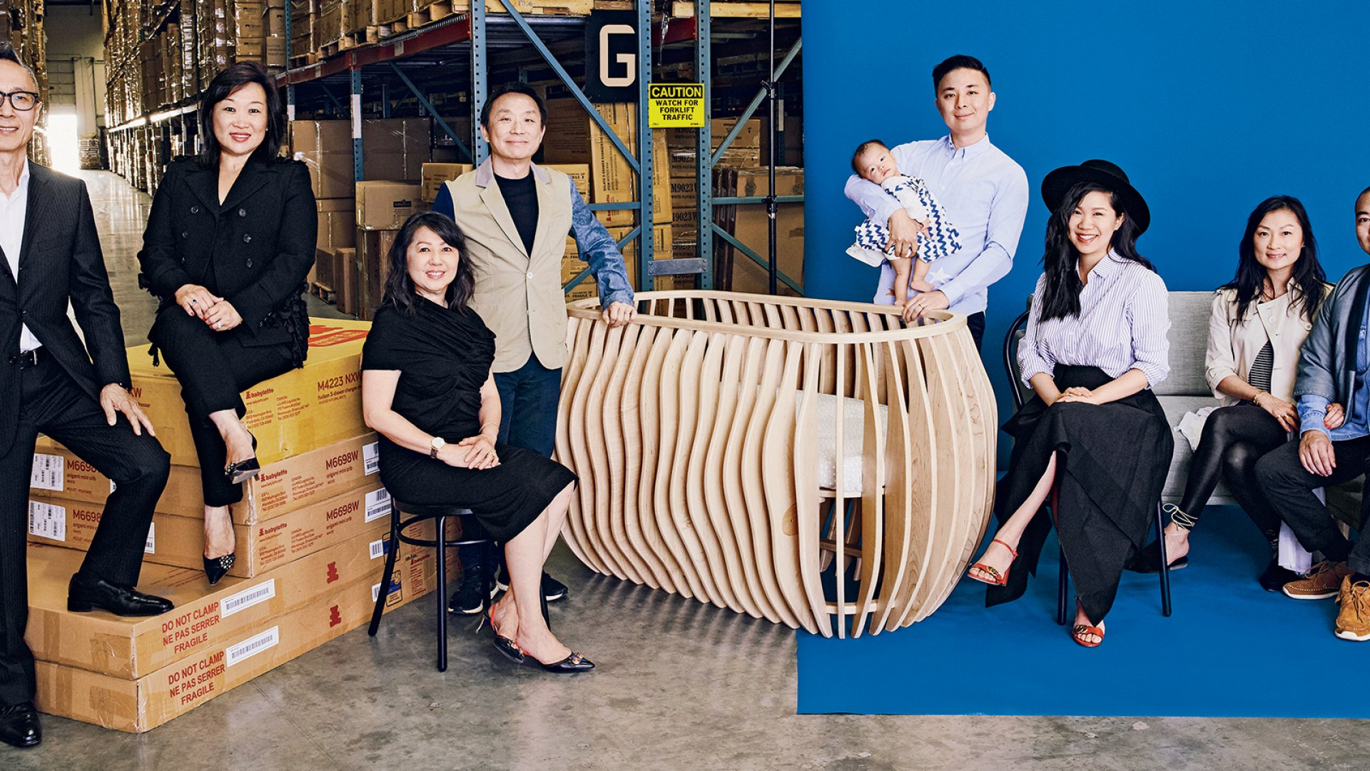 (From left) John Kwok, Julia Fong Yip, Maryann Fong, Daniel Fong, baby Sophie Fong, Teddy Fong, Tiffany Fong, Tracy Fong, and Eric Lin. The Montebello warehouse holds inventory of Million Dollar Baby's $7,500 Gradient crib, along with sofas from its new startup, Capsule Home.