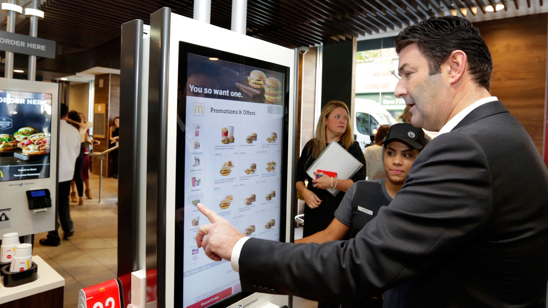 McDonald's CEO Steve Easterbrook demonstrates an order kiosk, with cashier Esmirna DeLeon, during a presentation at a McDonald's restaurant in New York's Tribeca neighborhood, Thursday, Nov. 17, 2016. On Thursday, the company said it wants to makes its fast-food outlets feel more like restaurants, with plans to eventually expand table service across its U.S. locations.