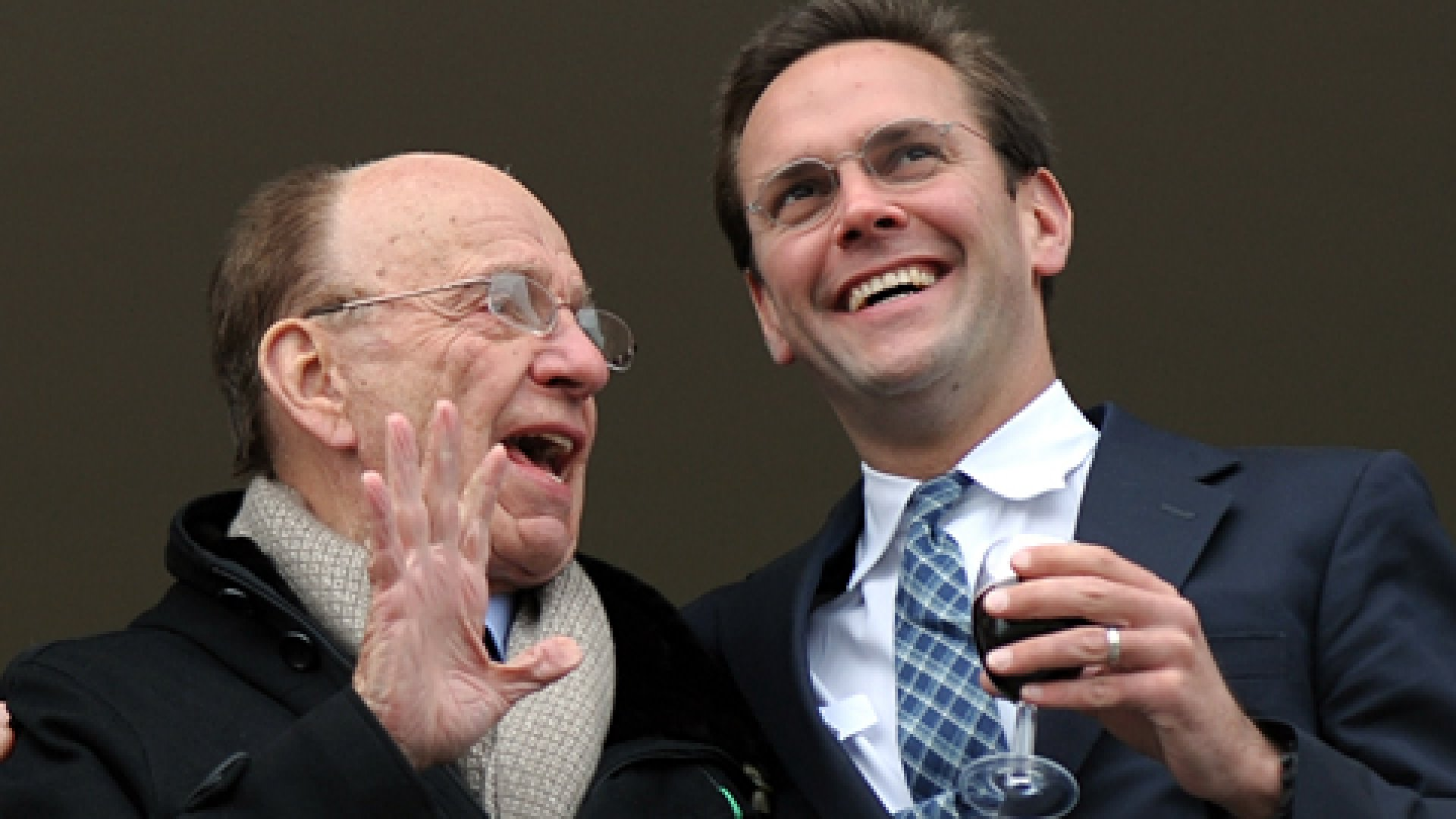 Media mogul Rupert Murdoch stands beside son James Murdoch on a balcony overlooking a Cheltenham Festival horse race in March 2010.
