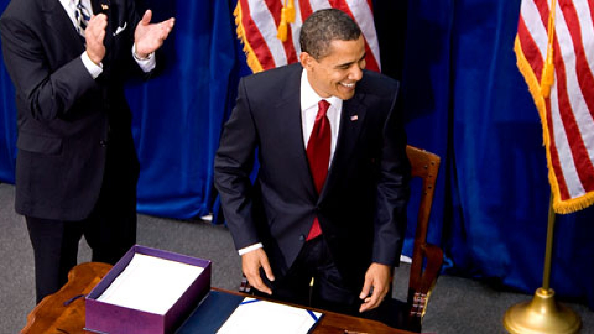Vice President Joe Biden, left, applauds after U.S. President Barack Obama signed an economic stimulus package into law inside the Museum of Nature and Science in Denver, Colorado, U.S., on Tuesday, Feb. 17, 2009.