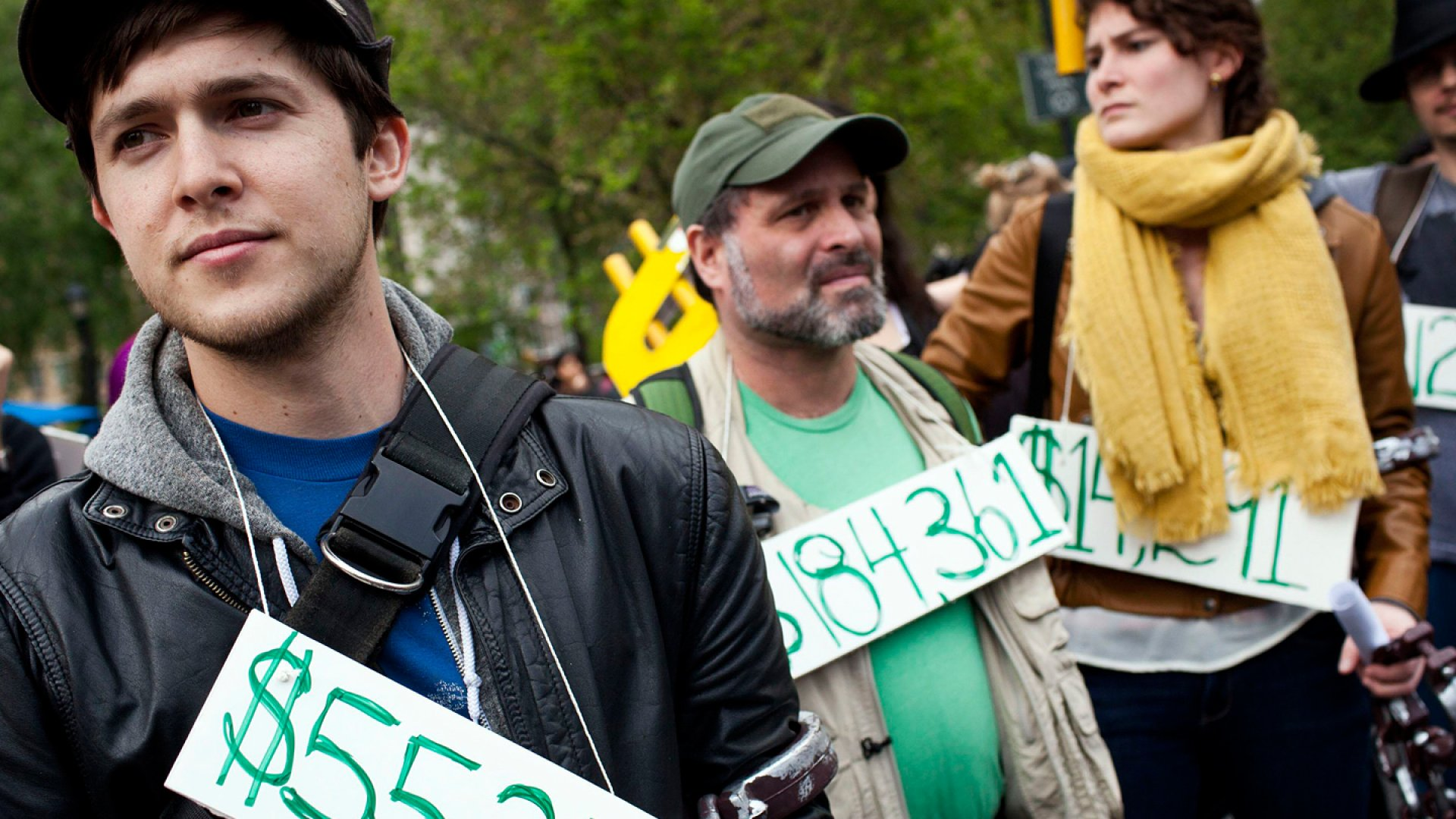 Occupy Wall Street demonstrators participating in a street-theater production wear signs around their necks representing their student debt during a protest in Union Square, in New York City.
