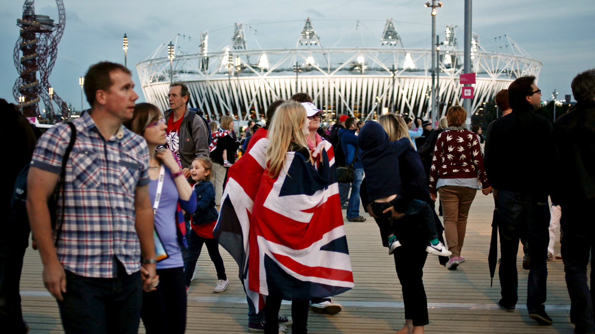 People walk in front of the Olympic stadium at the Olympic park of London during the 2012 Olympic Games.