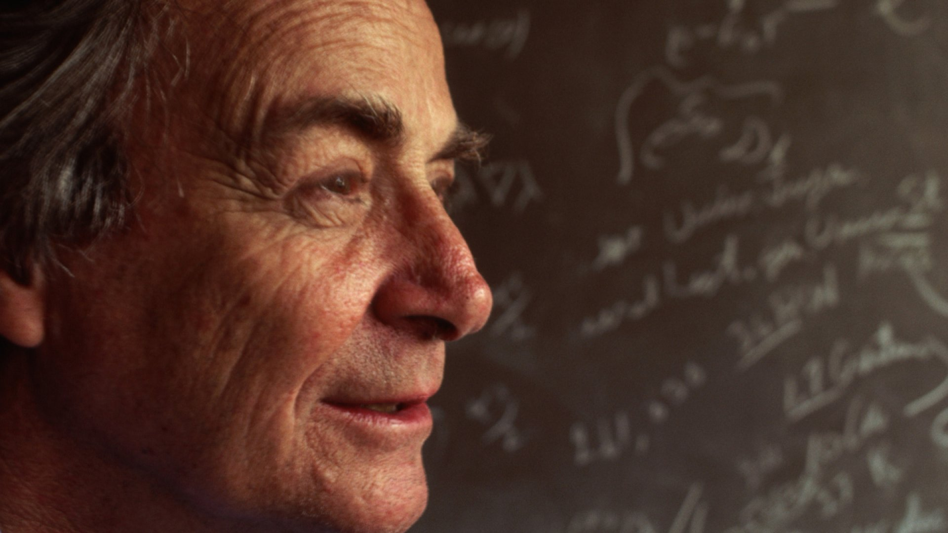 Feynman stands in front of a blackboard strewn with notation in his lab in Los Angeles, Californina.