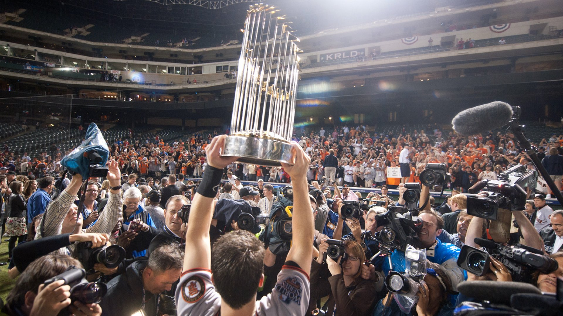 Buster Posey #26 of the San Francisco Giants celebrates by holding up the World Series Trophy after defeating the Texas Rangers in Game Five of the 2010 MLB World Series at Rangers Ballpark in Arlington, Texas on November 1, 2010.