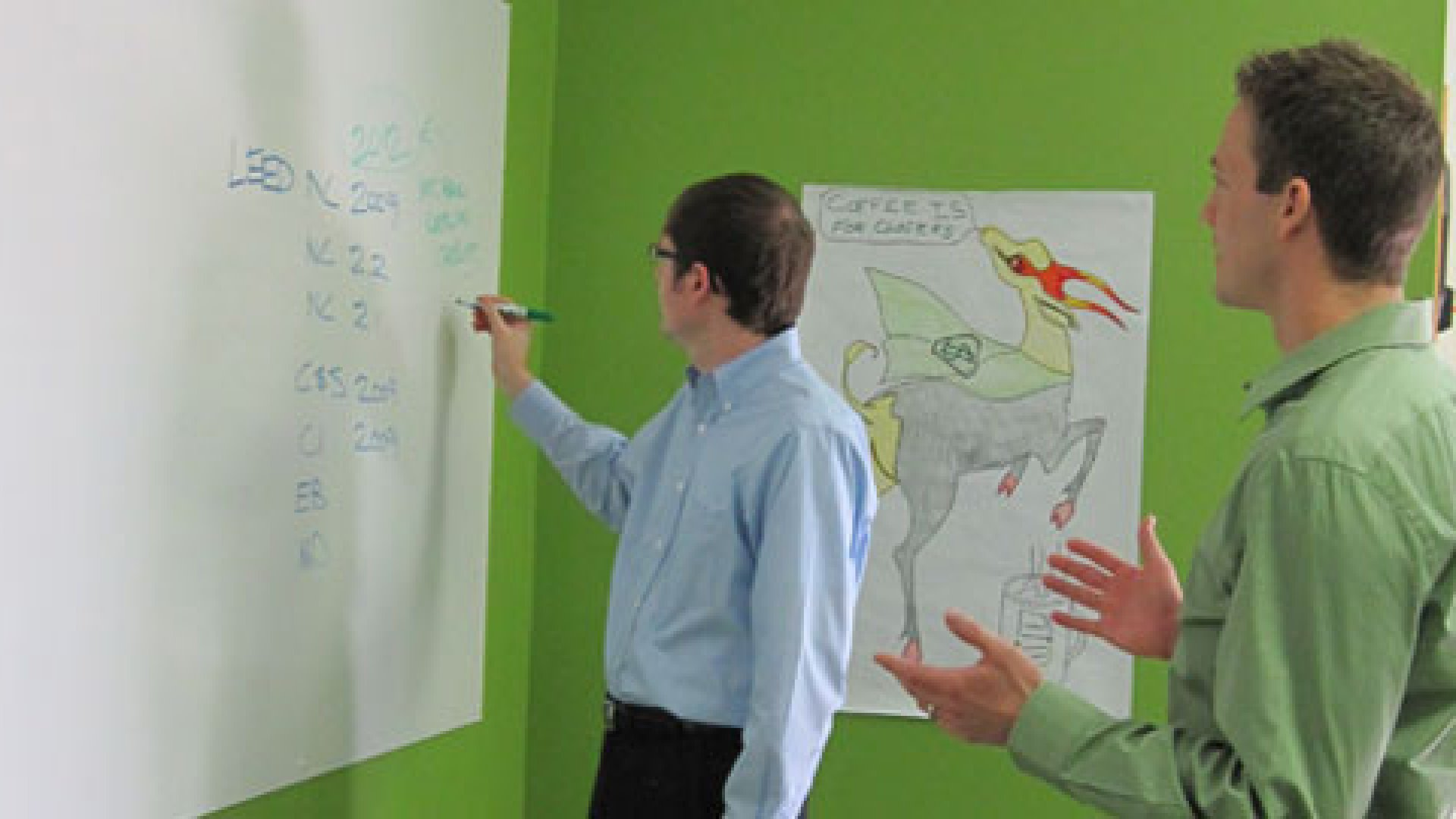 Submittal Exchange's president Matt Ostanik (left) and sales representative Brett Robben (right) discuss planning for their LEED® green building software product.  In the background is picture of a gazelle, the company's unofficial mascot representing fast-paced growth.