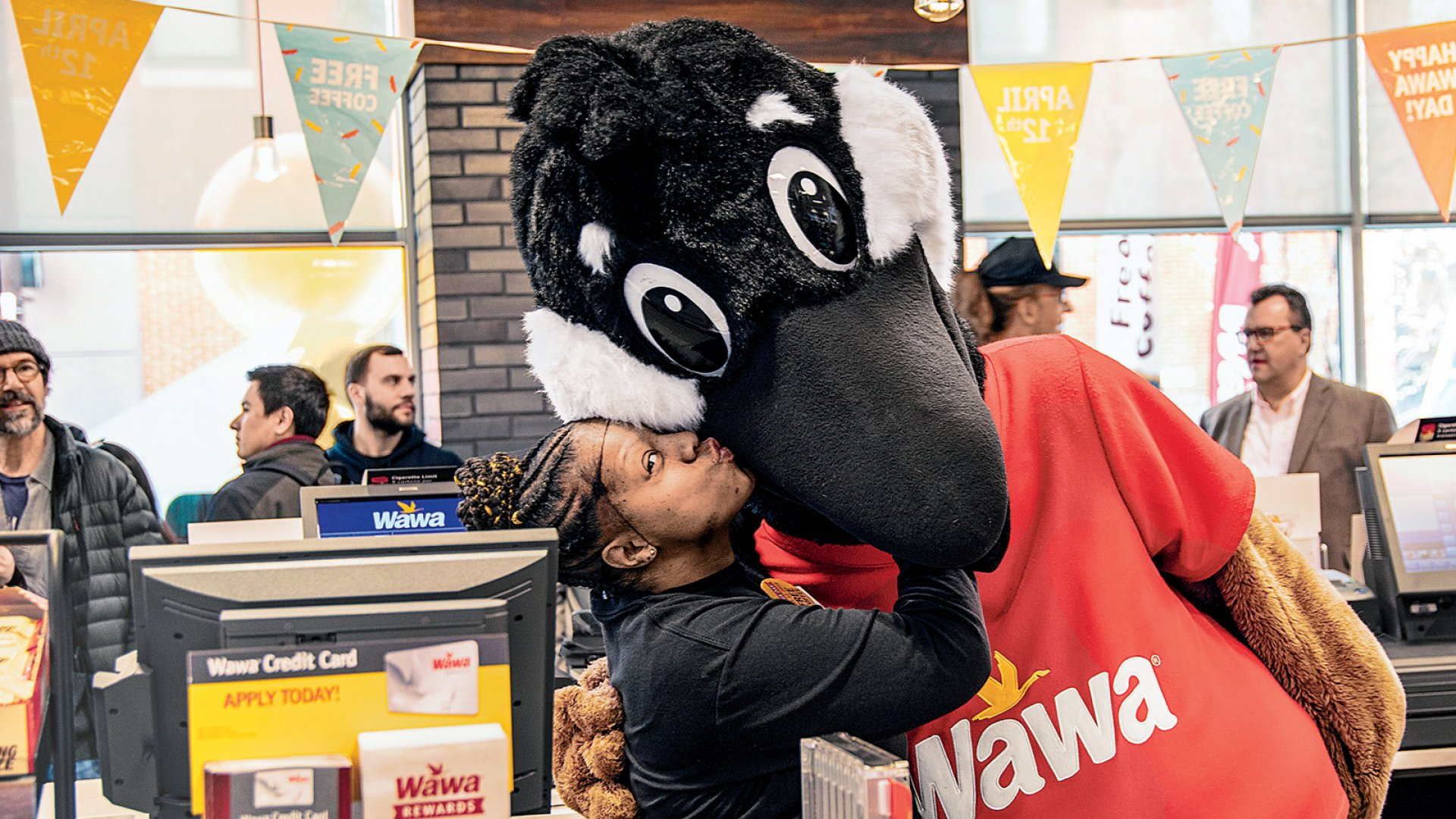 Wawa employee Towanda Davis and the company mascot, Wally Goose (<i>wawa</i> is the Ojibwe word for a Canadian goose), feeling the love at the opening of a Wawa store near Center City, Philadelphia. The company declared Wawa Day on April 12, in honor of the chain's 54th anniversary.