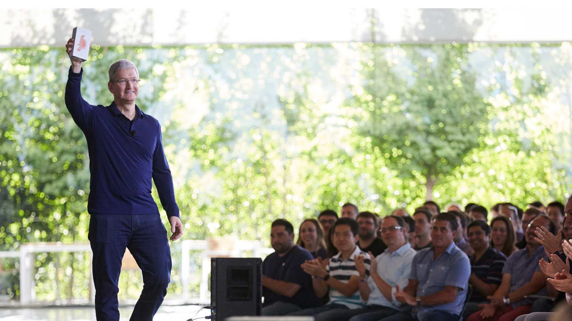 Tim Cook holds the one billionth iPhone, a 6s Plus model, in front of a cheering crowd.