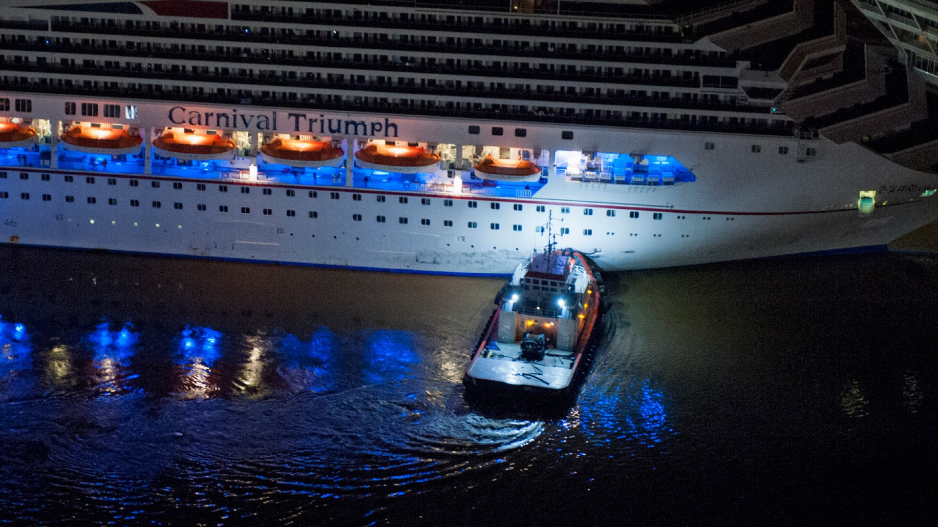 The crippled cruise liner Carnival Triumph limps into port guided by tug boats February 14, 2013 in Mobile, Alabama.