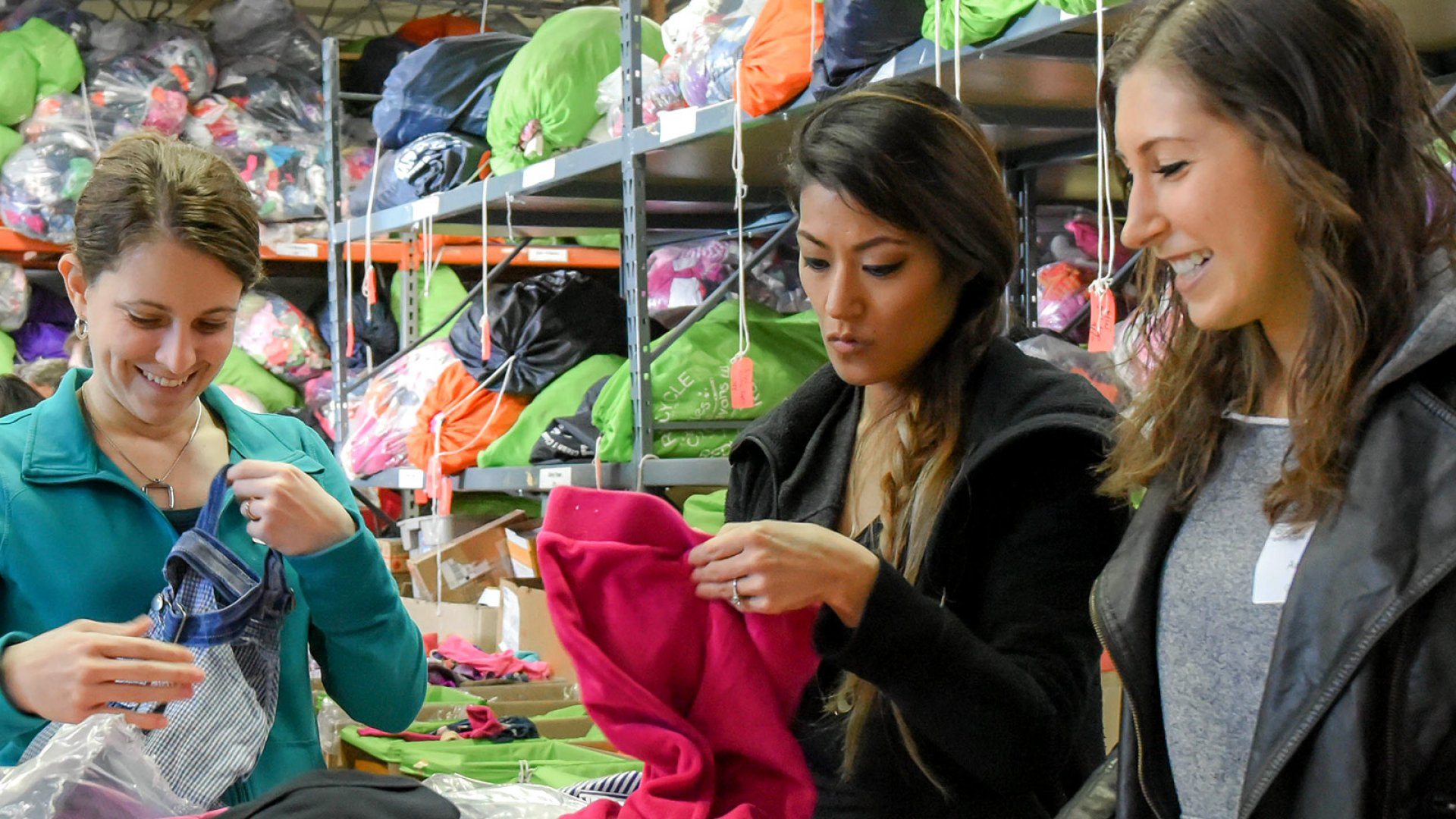 """As part of the """"Evolve Cares"""" program, Delinda Tinkey, Katherine Frank and Andrea Cascino sort clothes at Cradles To Crayons, an organization providing the children of low-income families with essential needs for home, school, and play."""