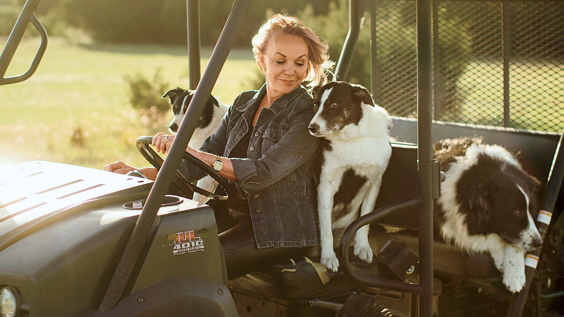 Gay Gaddis drives across her Texas ranch with three border collies.