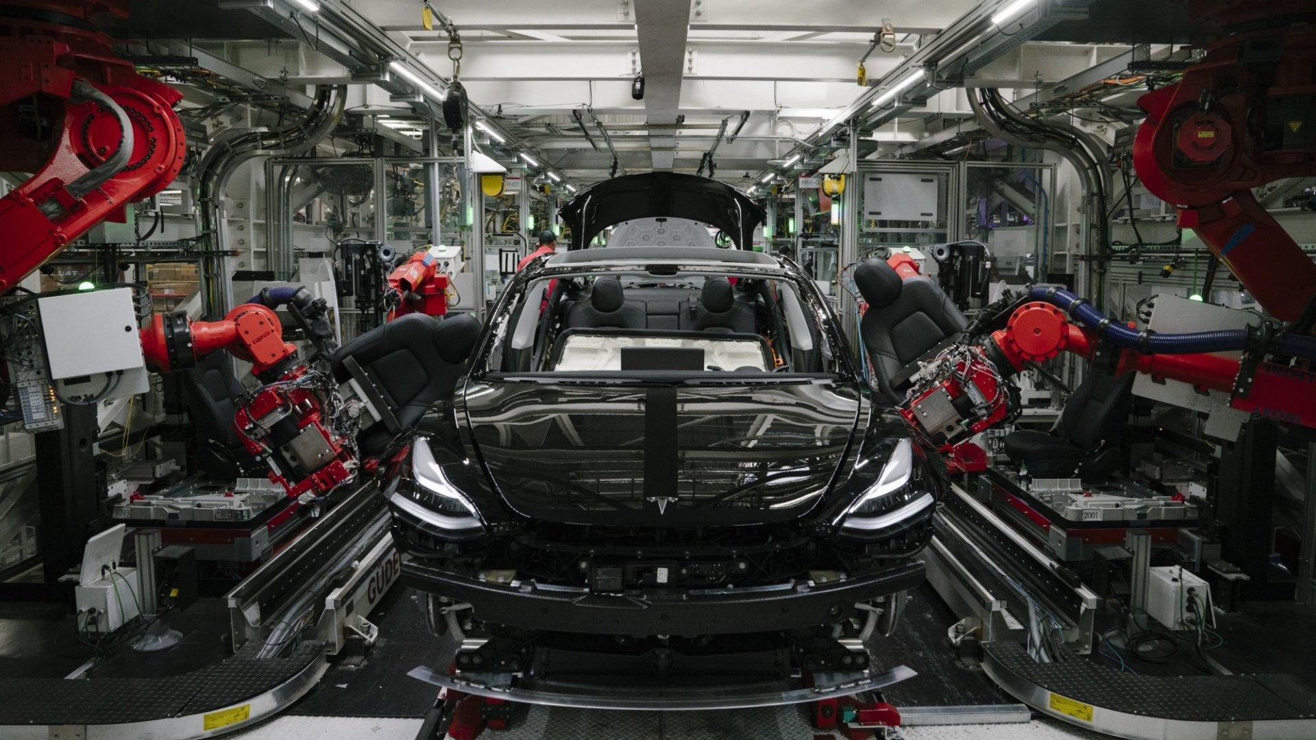 Robotic arms assemble a Model 3.