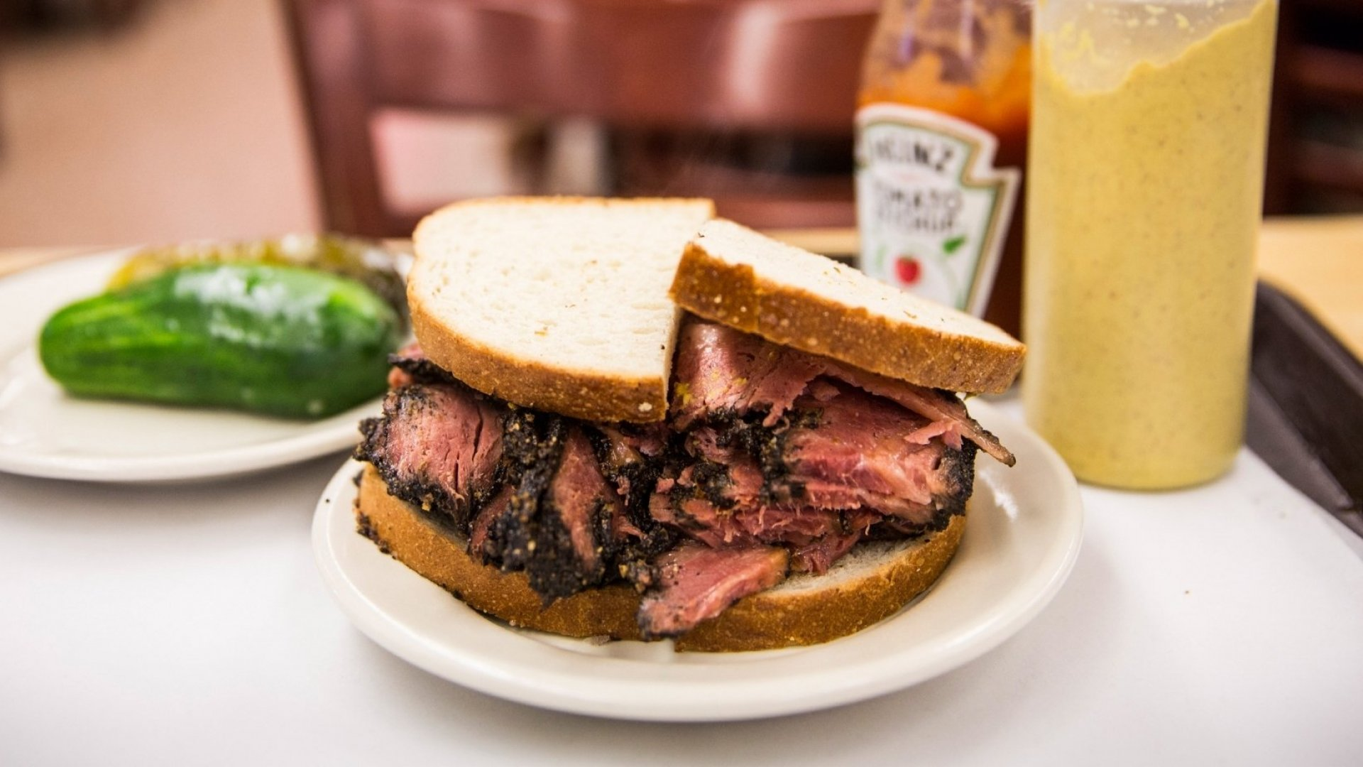 Katz's iconic pastrami sandwich with mustard and pickles.