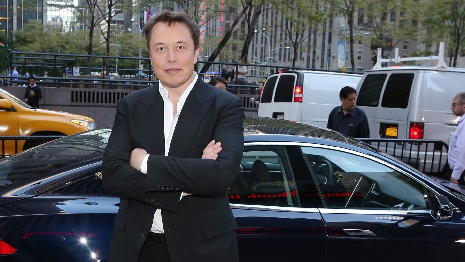 Elon Musk in front of a Tesla in New York City.