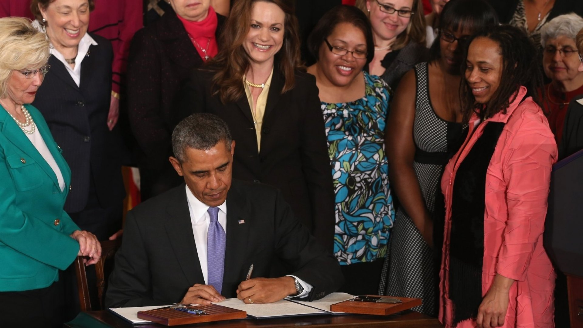 President Barack Obama signs a labor bill as women's right activist Lilly Ledbetter and other women look on.