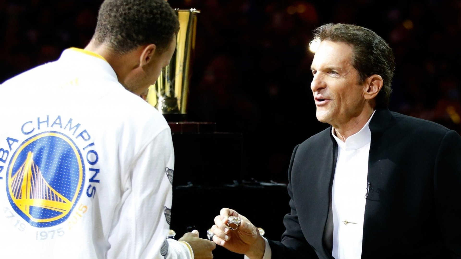 Golden State Warriors owner Peter Guber hands Stephen Curry #30 of the Golden State Warriors his championship ring