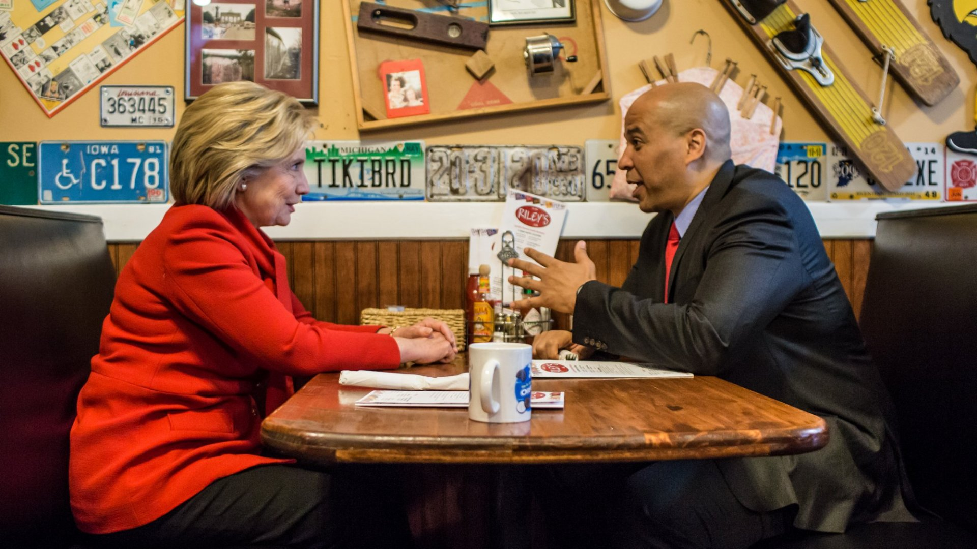 Democratic presidential candidate Hillary Clinton (L) talks with Sen. Cory Booker (D-NJ) at Riley's Cafe on January 24, 2016 in Cedar Rapids, Iowa. (Photo by Brendan Hoffman/Getty Images)