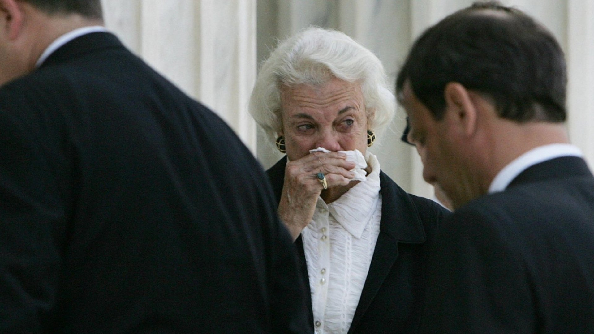 Sandra Day O'Connor looks on as pallbearers carry William Rehnquist's casket up the steps of the Supreme Court